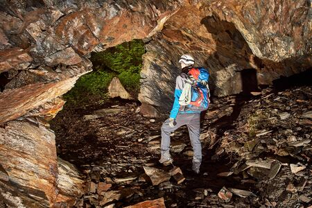 Young speleologist exploring a cave Stock Photo