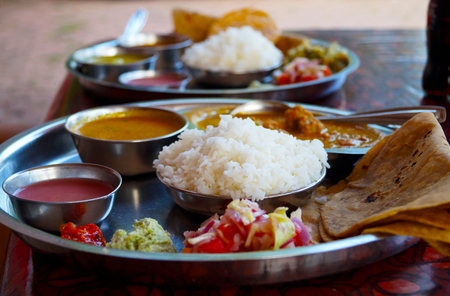 Traditional indian food - thali: rice, souces, spices, chapati, chicken and vegetables
