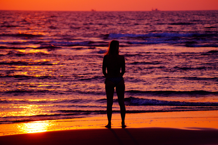 Woman standing on the beach and looking to the sunset. Female in bikini on the beach. Woman silhouette. Fitness model with sport body.