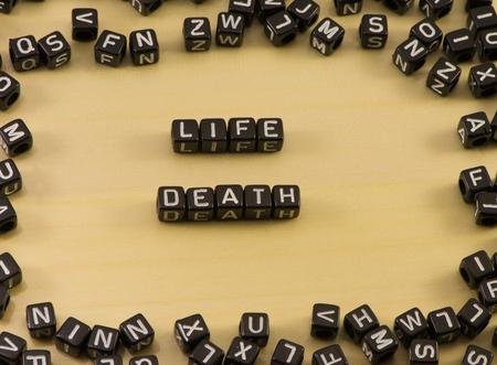 The word life and death on wood background