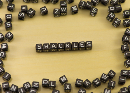 captives: The word shackles on wood background