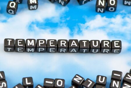 The word temperature on the sky background