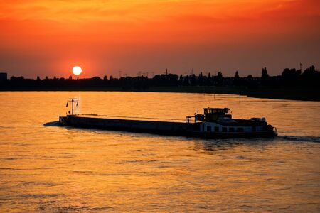 barge: Barge with cargo at sunset