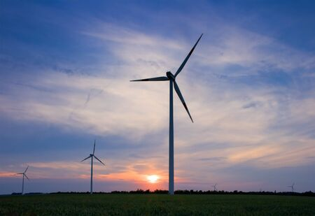 Wind turbines against setting sun photo