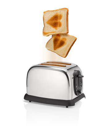heart burn: Freshly roasted bread pops out from a toaster with heart shaped burn marks.