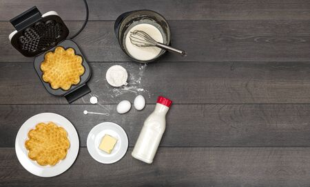waffle: Preparation and making of waffles, the needed ingredients, on dark wooden table seen from above, Stock Photo