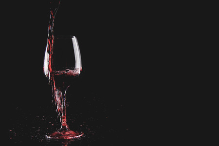 Pouring wine into glass but the wine is spilled Imagens