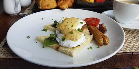 Poached eggs on two pieces of toast, sausage and tomato. Banque d'images