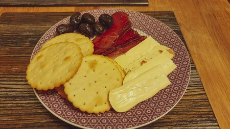 Sliced meat and cheese, olives and crackers. Archivio Fotografico