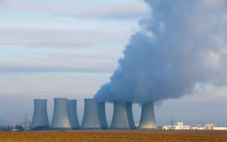 Nuclear power plant by day with smokestack