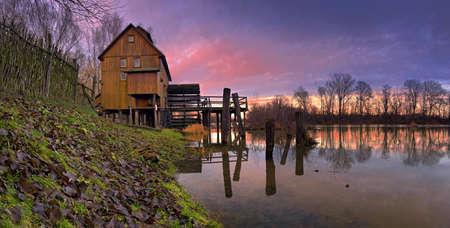 molino de agua: La salida del sol sobre el molino de agua de madera vieja Foto de archivo