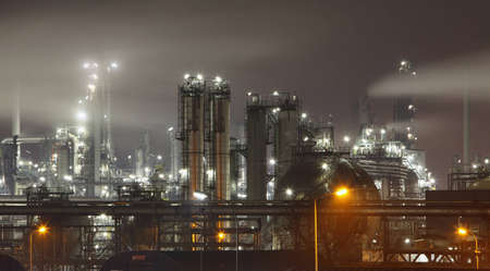 Petrochemical plant in night with smokestack photo