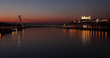 Bratislava castle and novy bridge a t sunset with reflection