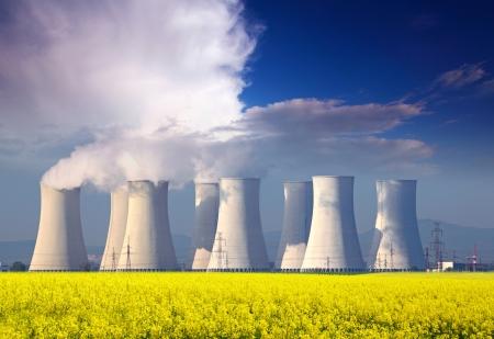 residuos toxicos: Central nuclear con el campo amarillo y grandes nubes de color azul