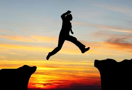 überleben: Silhouette von Wander-Frau springt �ber die Berge bei Sonnenuntergang
