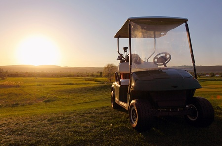 Golf cart over nice green and sunset photo