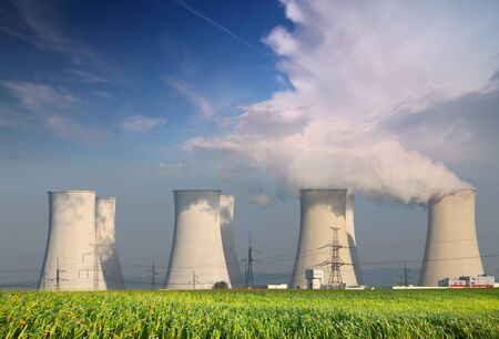 Nuclear power plant with yellow  field and big blue clouds Stock Photo - 16466127