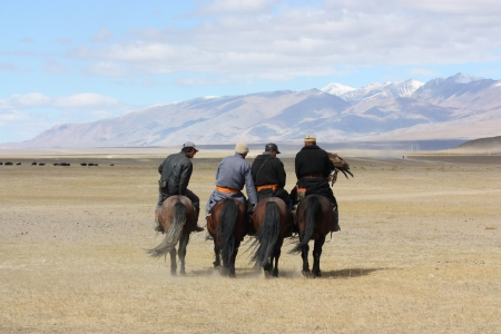 nomadism: Mongolians horsemen in traditional clothing with golden eagles during the festival of name  The Golden Eagle Festival  July 25, 2011, Mongolia - desert Stock Photo