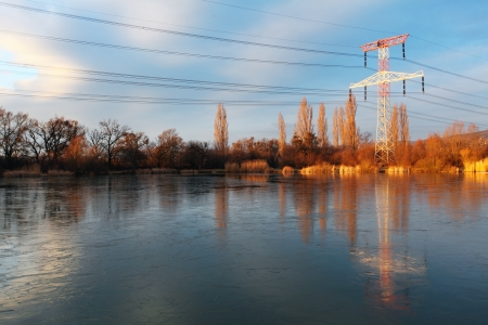 Electricity pylon with reflection in water photo
