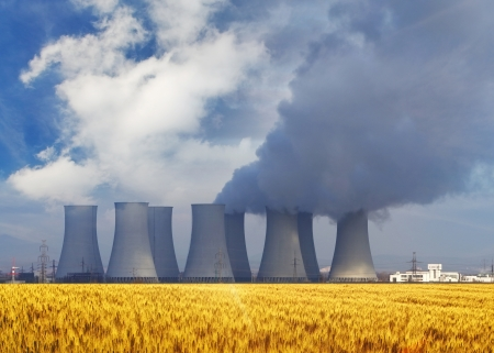 Nuclear power plant with yellow field and big blue clouds  Stock Photo - 16590650