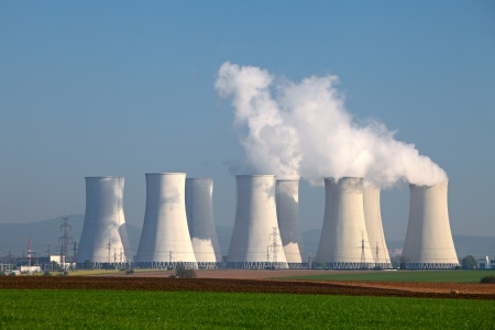electric power station: Nuclear power plant with yellow field and big blue clouds Stock Photo