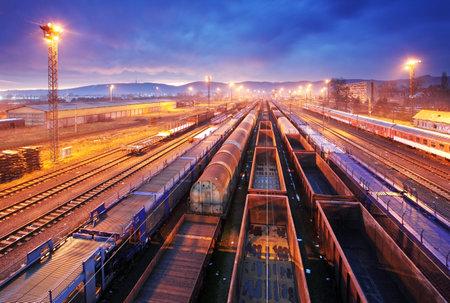 Nákladní vlak plošina při západu slunce se zásobníkem