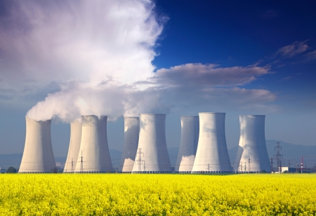 Nuclear power plant with yellow field and big  blue clouds  Stock Photo - 17298623