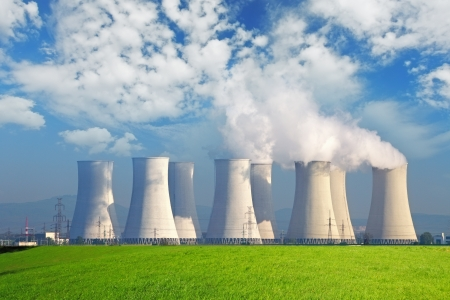 cooling towers: Nuclear power plant with yellow field and big blue clouds Stock Photo
