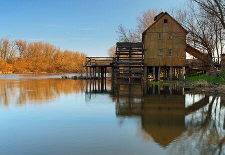 molino de agua: Río reflexión con molino de agua y el árbol Foto de archivo