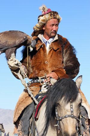 horseman: MONGOLIA - 25 luglio Il cavaliere mongolo anziano in abiti tradizionali con aquila reale durante il festival di nome The Golden Eagle Festival 25 Luglio 2011, la Mongolia - Deserto Editoriali