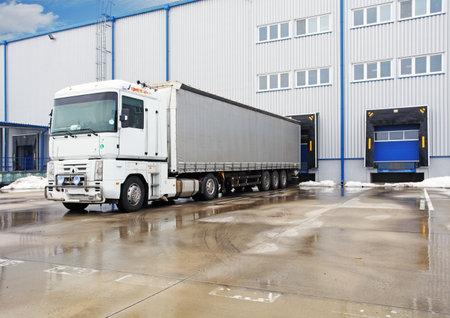 carretillas almacen: Descarga de grandes camiones contenedores en el edificio de almacén