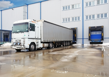 commercial docks: Unloading big container trucks at  warehouse building