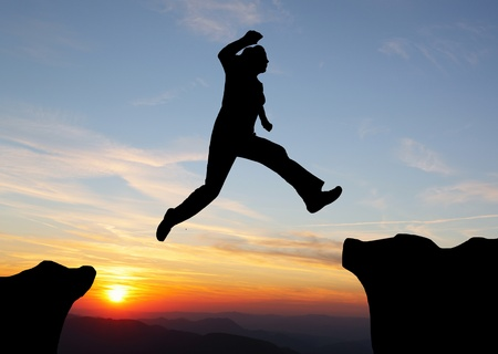 Silhouette of hiking man jumping over the mountains at sunset photo