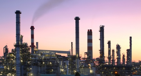 Oil refinery factory silhouette over sunset photo