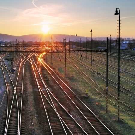 railroad station platform: Railroad with train at sunset and many lines Stock Photo