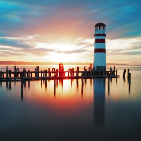 Ocean sunset with lighthouse photo