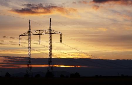 Pylon energii elektrycznej na zachodzie słońca - energia moc Zdjęcie Seryjne