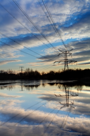horizon reflection: Electricity pylon with reflection in water at sunset