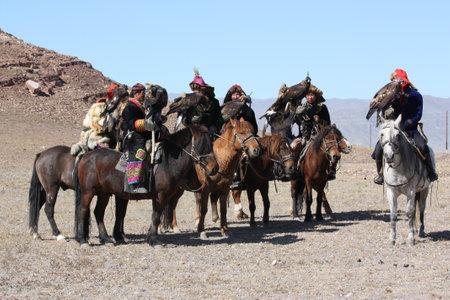 nomadism: MONGOLIA - 25 JULY: Senior Mongolians horsemen in traditional clothing with golden eagles during the festival of name The Golden Eagle Festival July 25, 2011, Mongolia - desert Editorial