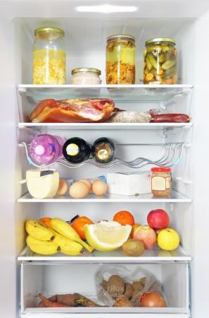 frigo: Koelkast geopend volledige gevulde up geladen met voedsel en verse ingrediënten Stockfoto