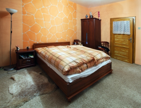 Orange Bedroom with a double wood bed photo