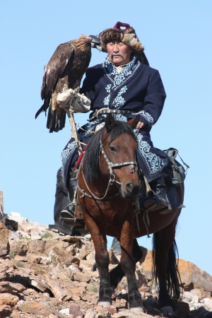 MONGOLIA - 25 JULY  The senior Mongolian horseman in traditional clothing with golden eagles during the festival of name  The Golden Eagle Festival  July 25, 2011, Mongolia