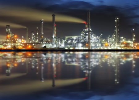 Oil refinery at night with reflection in water photo