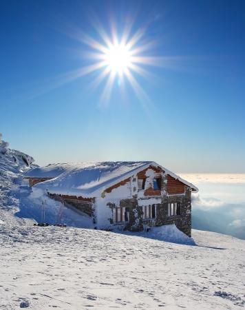 wintertime: Fairy tale building in wintertime with sun - Kamenna chata