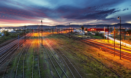 Railroad track at night with colorful sky photo