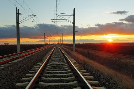 railway track: Railway at a sunset with sun and clouds