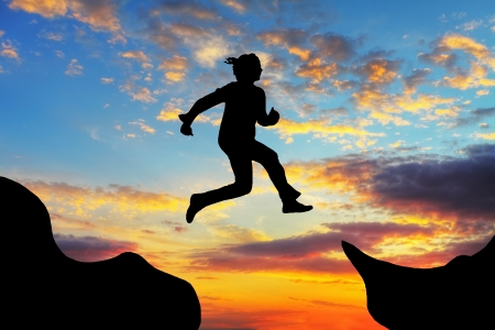 leap: Woman jump over canyon at a sunset