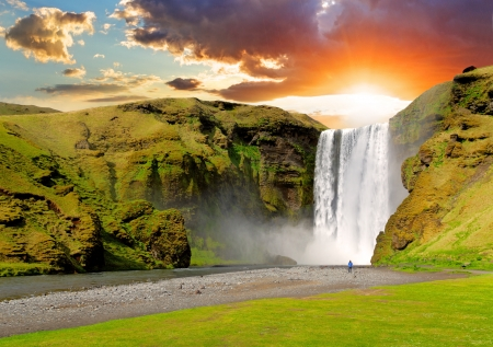 man waterfalls: famous waterfall Skogafoss in Iceland at sunset