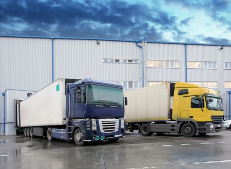 commercial docks: Unloading cargo truck at warehouse building Stock Photo