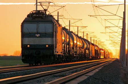 Trainen lading in spoorweg bij een zonsondergang